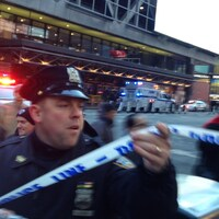 Un policier soulève une banderole de sécurité.