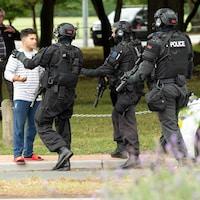 Des policiers s'adressent à un homme sur le trottoir.