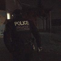 Un policier, devant un mur de graffitis.