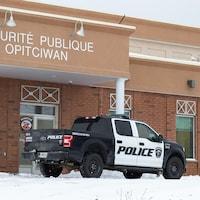 Une camionnette garée devant un poste de police.