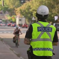 Un policier de dos portant un dossard au bord d'une rue de Québec.
