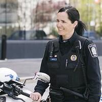 Une femme policière tient le guidon de sa motocyclette.