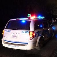 Une voiture de police la nuit, avec ses gyrophares allumés.