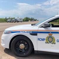 Un policier de la GRC, assis dans son véhicule près d'une autoroute, utilise un radar.