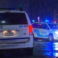 Deux fourgonnettes de policiers sont stationnées dans une rue résidentielle de Montréal en pleine nuit.