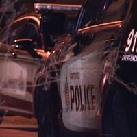 Deux voitures de police de Vancouver garées, de nuit, avec logo 911 visible au premier plan.