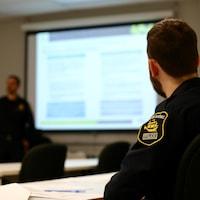 Un policier du Service de police de la Ville de Québec est assis dans une salle de formation.