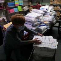 Une femme dépouillant des bulletins de vote.