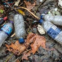 Des bouteilles de plastique vide traînant sur le sol mouillé.