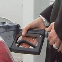 Une personne tient le pistolet d'une pompe à essence qui est inséré dans l'entrée du réservoir de sa voiture.