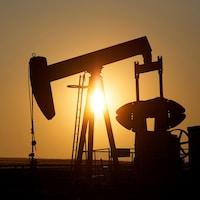 La silhouette d'un puits de pétrole devant un soleil couchant.