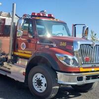 Un camion de pompier stationné devant une caserne.
