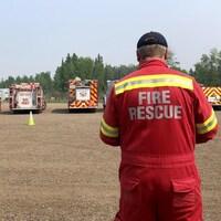 Un pompier est debout avec devant lui sept camions de pompiers qui sont garés dans un parc de stationnement.