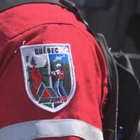Gros plan sur l'écusson de la SOPFEU sur l'épaule d'un pompier.