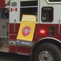 Un camion de pompier visite une fête d'anniversaire et le pompier du siège passager brandit une pancarte de souhait.