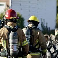 Trois pompiers en uniforme sur les lieux d'un incendie éteint.
