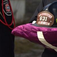 Le casque de pompier du défunt est posé sur un coussin violet, tenu par un pompier en uniforme de cérémonie.