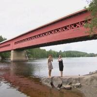 Des adolescents sont sur la rive près du pont couvert.