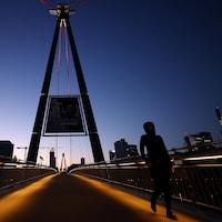 Deux personnes marchent à distance sur un pont piétonnier.
