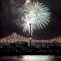 Des feux d'artifice éclatent au-dessus du pont Jacques-Cartier illuminé.