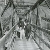Des enfants marchent sur un pont suspendu en bois enjambant une rivière.