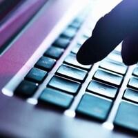Une main qui tape les touches d'un clavier d'ordinateur.