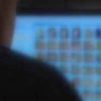 Un homme assis devant un écran rempli de visages floutés.