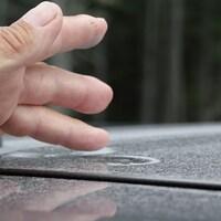 Un résident passe sa main sur une table à jardin couverte de poussière.