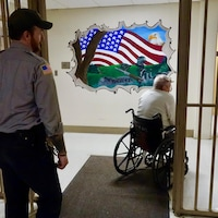 Un prisonnier âgé accompagné d'un gardien se déplace en fauteuil roulant dans le pénitencier Laurel Highlands, en Pennsylvanie