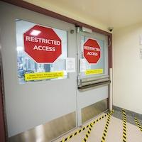 Une porte fermée avec deux gros panneaux Accès restreint dessus.