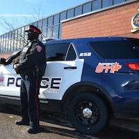 Un policier à côté d'un véhicule de patrouille devant le quartier général de la police de Thunder Bay.