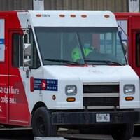 Un employé à bord d'un camion de livraison de Postes Canada stationné devant le centre de tri Gateway-Est.