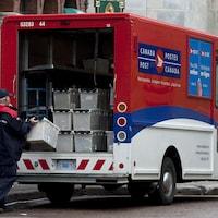 Un travailleur de Postes Canada sort une boîte de courrier d'un camion de livraison.