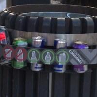 Une poubelle autour de laquelle est installé un support contenant plusieurs bouteilles consignées.