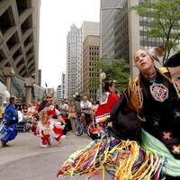 Une femme autochtone vêtue d'un costume traditionnel danse dans la rue.