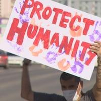 Une personne dans la rue et portant un masque tient une pancarte sur laquelle on peut lire « Protégez l'humanité ».