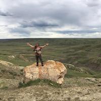 Joely BigEagle-Kequahtooway bras au ciel, sur un rocher, dans le Parc national des Prairies.