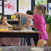 Des enfants jouent autour d'une table en compagnie d'une enseignante.