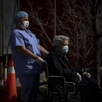 Une préposée avec un patient en fauteuil roulant, portant tous les deux un masque.