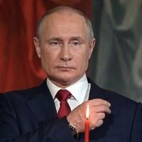 L'air solennel, Vladimir Poutine, vêtu d'un veston et d'une cravate, fait un signe de la croix avec sa main droite.