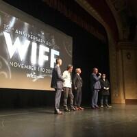 Cinq hommes debout sur une scène. Un d'entre eux a un micro à la main.