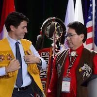 Le premier ministre revêt une veste autochtone en regardant Mike Mitchell.