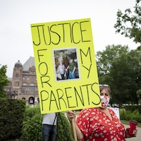 """Une femme tient un pancarte sur laquelle on voit une photo de ses parents avec l'inscription """"Justice for my parents"""". Derrière elle, on peut voir l'Assemblée législative au loin."""