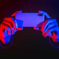 Deux mains tiennent un téléphone éclairées par des lumières rouges et bleues qui rappellent les gyrophares d'une voiture de police.