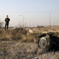 Un policier monte la garde alors que l'on voit les débris d'un avion ukrainien qui s'est écrasé à Shahedshahr, au sud-ouest de la capitale Téhéran.