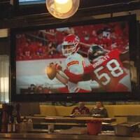 Deux joueurs de football en uniformes rouge et blanc apparaissent sur un écran géant dans un pub dont la salle à manger est quasi vide.