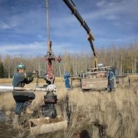 Un ouvrier utilise de la machinerie lourde près d'un puits.