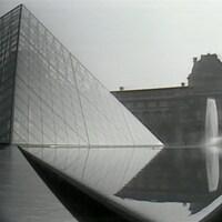 Perspective sur la pyramide de verre du Louvre encadré d'une fontaine et du bâtiment ancien original du Louvre.