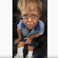 Un petit garçon de 9 ans assis dans une voiture regarde la caméra en pleurant.
