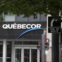 L'enseigne de Québecor derrière un panneau où il est écrit « voie de droite ».
